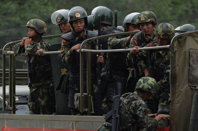 """Policías paramilitares chinos se preparan para viajar en camiones durante una ceremonia de """"demostración de fuerza"""" en Urumqi, el 29 de junio de 2013. El régimen chino está revisando las leyes para evitar las fugas de información militar. (MARCA RALSTON/AFP/Getty Images)"""