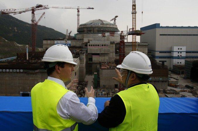 Ministro británico de Hacienda, George Osborne (izquierda) habla con el gerente general de la Nuclear Power Joint Venture en Taishan, Guo Liming delante de un reactor nuclear en construcción en una planta de energía nuclear en Taishan, provincia de Guangdong, el 17 de octubre de 2013. El régimen chino esta tratando de ganar varios contratos para construir instalaciones nucleares en otros países. (BOBBY YIP / AFP / Getty Images)
