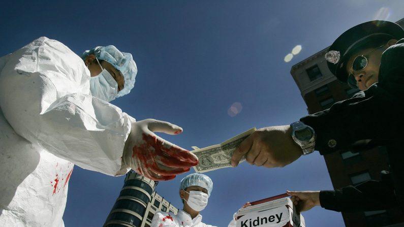 Practicantes de Falun Gong realizan una representación del comercio de órganos de prisioneros de conciencia que ocurrió en China, en Washington D.C., el 19 de abril de 2006. (Jim Watson/AFP/Getty Images)