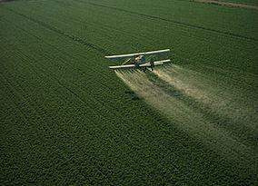Avioneta vertiendo plaguicidas sobre cultivos. (USDA -Charles O'Rear-Wikimedia Commons)