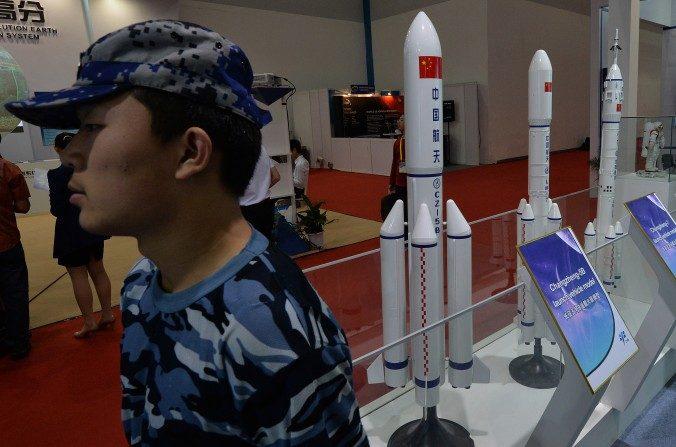 Un guardia de seguridad se encuentra junto a modelos de cohetes chinos exhibidos en Beijing el 24 de septiembre de 2013. El régimen chino está probando armas que pronto podrían poner en peligro los satélites en todas las órbitas. (Marcos Ralston / AFP / Getty Images)