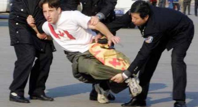 Policías del régimen chino secuestran a un practicante de Falun Dafa occidental que mostraba una bandera sobre la práctica de cultivación en la plaza Tiananmen, Beijing. (Minghui.net)