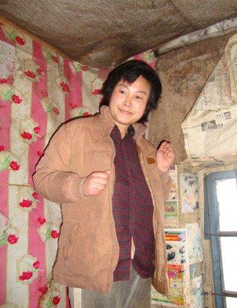 Liu Zhi Mei, sufriendo un colapso mental por la persecución, corrió a un rincón de su vivienda con los puños cerrados cada vez que alguien trató de acercarse a ella. (Minghui)