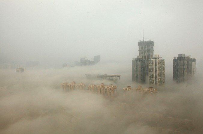 Edificios envueltos en la niebla de humo el 8 de diciembre de 2013, en Lianyungang, China.Investigadores chinos dicen que la fuerte contaminación está matando los bosques naturales de China. (ChinaFotoPress / Getty Images)