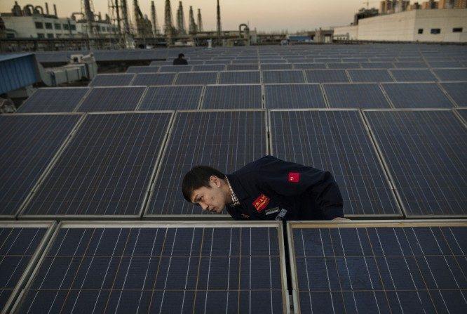 Un gerente de Yingli Solar verifica un panel solar en el techo de la sede de la compañía en Baoding, China, el 4 de diciembre de 2014. (Foto por Kevin Frayer / Getty Images)