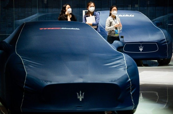 Mujeres de pie junto a coches Maserati delante de la 16ª Exposición Internacional de Shanghái sobre la Industria automotriz, el 19 de abril de 2015. (JOHANNES EISELE / AFP / Getty Images)