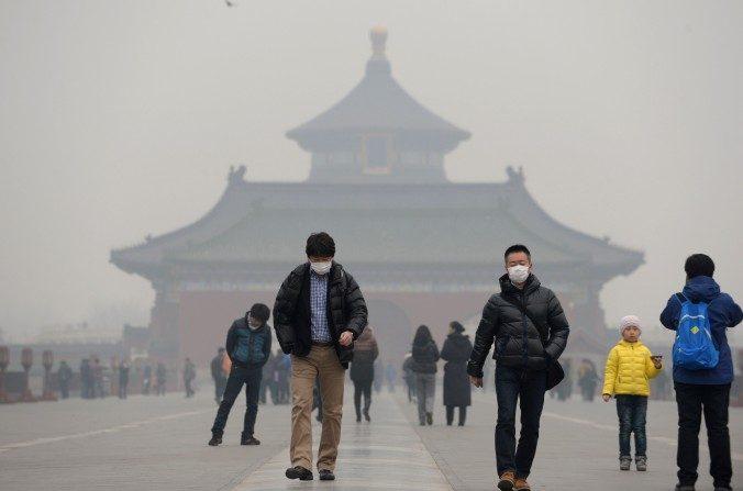Esta imagen tomada el 24 de febrero de 2014 muestra a los visitantes llevando máscaras en el Templo del Cielo cubierto de neblina en Beijing. (STR / AFP / Getty Images)
