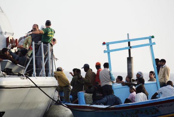 Inmigrantes ilegales africanos aguardan en un maltrecho bote de madera a que las guardias costeras italianas los rescaten.  (Photo by Marco Di Lauro/Getty Images)