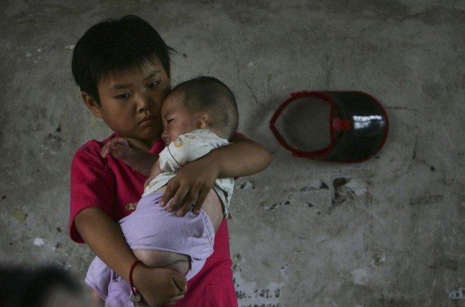Wang Huaixue sostiene un bebé en el orfanato Wang Jiayu el 9 de julio de 2006 en la provincia de Anhui. Millones de huérfanos oficiales y no oficiales son las víctimas del sistema social chino. (China Photos / Getty Images)