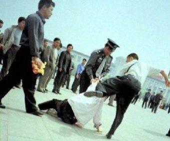 La Tiranía capturada por la camera: Policías uniformados y de civil arrestando a un practicante Falun Gong, quien había ido a la plaza Tiananmen, para apelar pacíficamente por el fin de la persecución, 25 Julio, 2001. (Clearwisdom)
