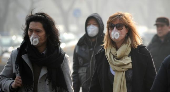 El cáncer al Pecho es el de mayor incidencia e las mujeres de América. Estudios revelan que influye el aire que se respira antes de su primera lactancia, En la fotografía, mujeres están llevando mascarillas mientras caminan por las calles de Beijing el 16 de enero de 2014. Científicos chinos identificaron 1.315 especies de microorganismos en el contaminado aire de la capital china. (Wang Zhao/AFP/Getty Images)