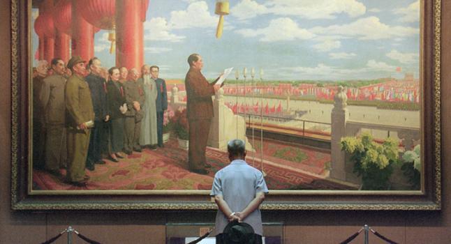 Un hombre chino mira una pintura del líder comunista Mao Zedong declarando la formación de la República Popular de China, en la puerta de la ciudad prohibida en 1949. A pesar de que el Partido Comunista Chino clama lo contrario, la historia del PCCh está llena de engaños y de la sangre de inocentes. (Foto: GOH CHAI HIN/AFP/Getty Images)