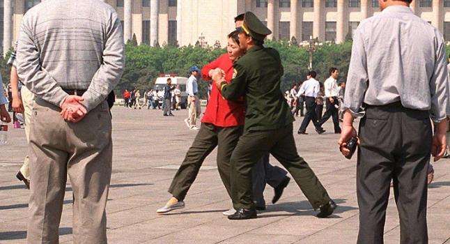Comentario 9: La Policia arrestando a los practicantes de Falun Gong quienes apelan pacíficamente en la Plaza Tiananmen el 11 de Mayo, 2000. (AFP/Getty Images)