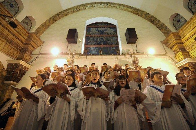 Devotos chinos cantan himnos durante la misa de Nochebuena en una iglesia católica en Pekín el 25 de diciembre de 2012. (Wang Zhao / AFP / Getty Images)