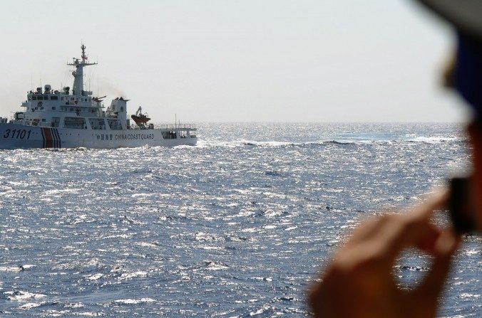 Un oficial de la guardia costera vietnamita toma una foto de un barco de la Guardia Costera de China en el Mar Meridional de China el14 de mayode 2014, fuera de la costa central de Vietnam. El régimen chino está defendiendo ahora el espacio aéreo sobre la región. (Hoang Dinh Nam / AFP / Getty Images)
