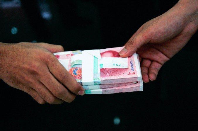 Un empleado pasa un fajo de yuanes chinos a otro empleado en un banco el 22 de julio de 2005 en Beijing, China. (China Photos/Getty Images)