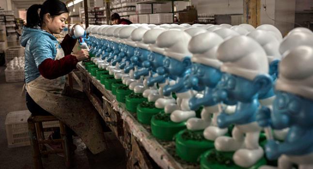 """Una trabajadora china pinta productos de """"Los Pitufos"""" en la fábrica de cerámica Shunmei Group (SMG) en Dehua, provincia de Fujian, China, el 7 de diciembre de 2014. Empresarios industriales argentinos temen que una profundización de las relaciones con China, ante las precarias condiciones laborales del país asiático, permitan una oleada de importaciones del gigante asiático y destruyan producción y empleo locales. (Kevin Frayer / Getty Images)"""