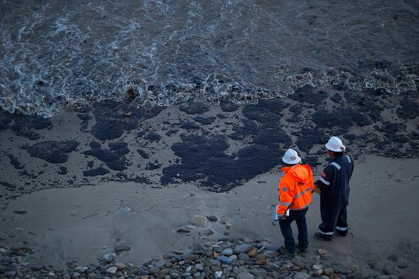 Oficiales caminan por una playa cubierta de petróleo el 19 de mayo 2015 al norte de Goleta, California. Foto:  David McNew/Getty Images