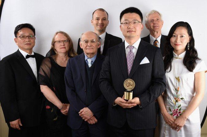 """El director Leon Lee sostiene el premio junto con otras personas que trabajaron en la premiada película """"Cosecha Humana"""" en la 74a ceremonia de los Premios Anuales  Peabody en 2015. (Cindy Ord / Getty Images para los Premios Peabody)"""