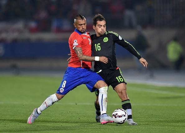 El mediocampista chileno Arturo Vidal (izq) y el defensor mexicano Adrián Alderete en el partido por la Copa América 2015. (RODRIGO ARANGUA/AFP/Getty Images)