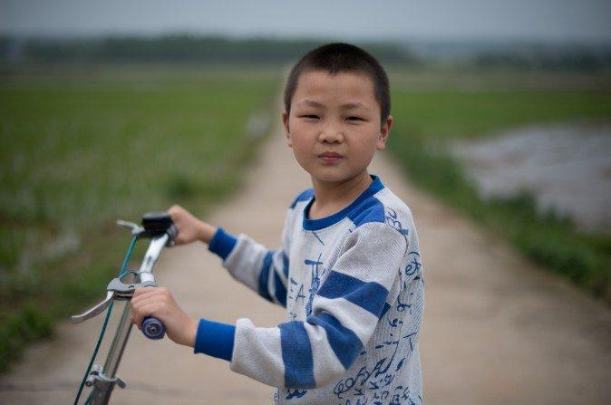 Un niño, cuyos padres son trabajadores migrantes, posa junto a su bicicleta en el poblado de Zhuangshuzui, provincial de Hunan, el 30 de abril del 2013. (Ed Jones/AFP/Getty Images)