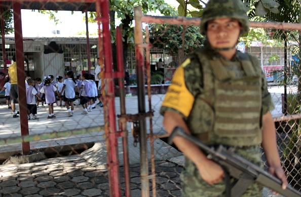 Un soldado monta guardia fuera de un jardín de infantes en Ciudad Renacimiento en Acapulco, México, durante una operación de seguridad para proteger a los profesores y estudiantes de las pandillas que exigen pagos de extorsión, el 19 de febrero de 2015. (Pedro PARDO / AFP / Getty Images)