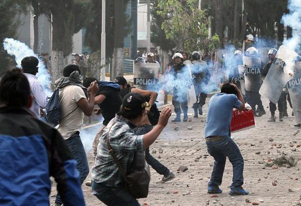 Manifestantes chocan con la policía peruana de Arequipa el 14 de mayo de 2015, oponiéndose al proyecto minero Tía María, valuado en 1.400 millones de dólares, en el sur de Perú, 1100 km al sur de Lima, lo que podría afectar a los agricultores de la región. Las protestas han dejado tres muertos en los 50 días. (STR / AFP / Getty Images)