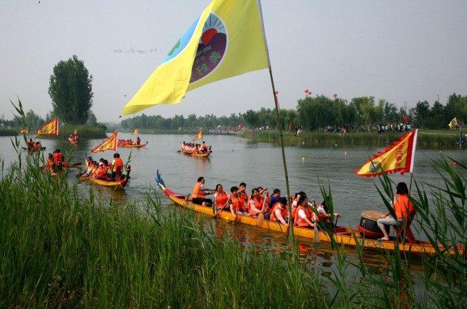 Botes de dragón en la carrera anual que se realiza en el río Binzhou, en la provincia china de Shandong, 20 de junio de 2015. (STR/AFP/Getty Images)