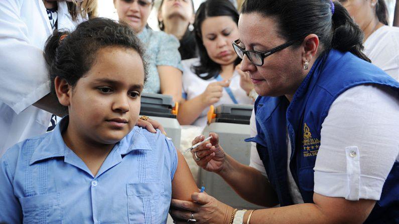 Una niña siendo vacunada contra el virus del papiloma humano (VPH) por los empleados del Ministerio de Salud en Tegucigalpa, el 17 de mayo de 2016. (ORLANDO SIERRA / AFP / Getty Images)