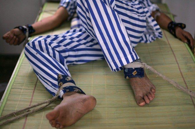 Enfermo con brazos y piernas atados a cama en el Hospital mental Anxian, condado de Anxian, provincia de Sichuan (China), el 24 de agosto del 2008. (China Photos/Getty Images)