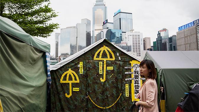 Una mujer frente a una tienda de campaña con el símbolo del movimiento democrático, el paraguas amarillo, frente a la sede del gobierno de Hong Kong, 15 de junio de 2015. (Dale de la Rey/AFP/Getty Images)
