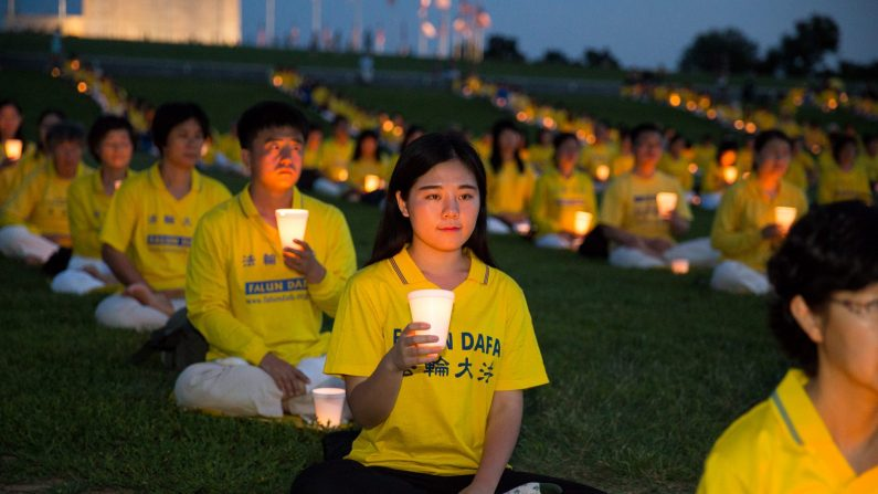 Practicantes de Falun Dafa realizan una vigilia conmemorativa en el aniversario del comienzo de la persecución en China, en Washington DC, en julio de 2015. (Larry Dye/La Gran Época)