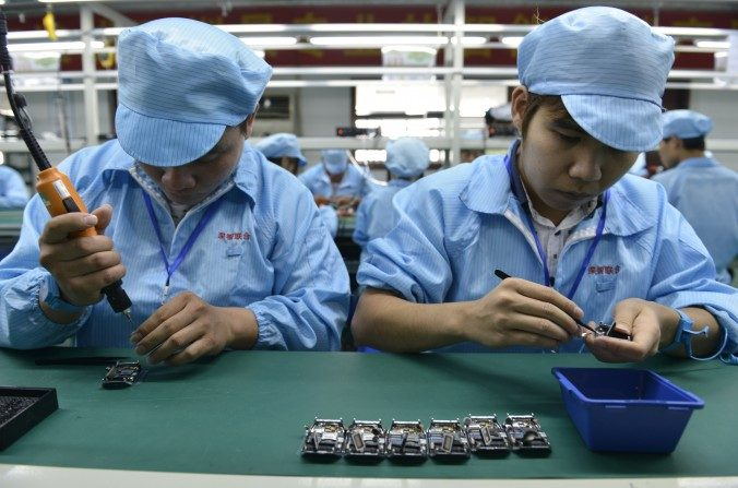 Trabajadores chinos ensamblan relojes inteligentes baratos en una fábrica en Shenzhen, en la provincia meridional china de Guangdong, antes del lanzamiento del reloj de Apple el 24 de abril. (STR / AFP / Getty Images)