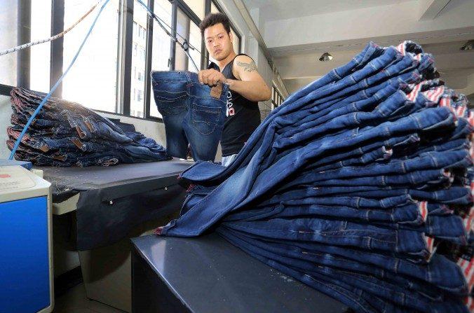 Esta imagen tomada el 12 de mayo del 2015 muestra a un trabajador chino haciendo pantalones en una fábrica de ropa en Shishi, provincia de Fujian, este de China. (STR/AFP/Getty Images)