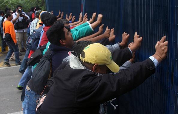 Los profesores de la CNTE empujan la puerta del aeropuerto de Oaxaca durante una protesta contra la reforma educativa, en Oaxaca, México, el 3 de junio de 2015. (PATRICIA CASTELLANOS / AFP / Getty Images)