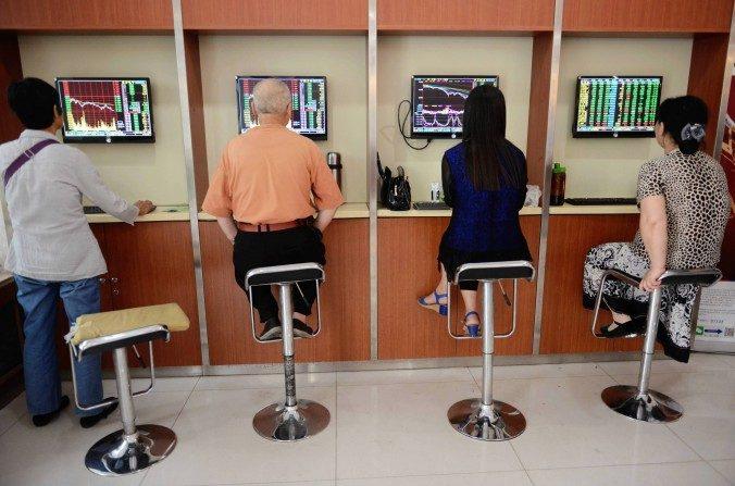Inversores bursátiles chinos reaccionan mientras comprueban los precios de las acciones en una empresa de valores en Fuyang, en la provincia de Anhui de China el19 de juniode 2015. (STR / AFP / Getty Images)