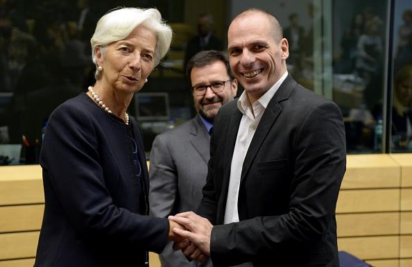 El ministro de Finanzas de Grecia Yanis Varoufakis (Der.) se da la mano con  la Directora del FMI (Fondo Monetario Internacional) Christine Lagarde, antes de una reunión del Eurogrupo celebrada en el edificio Lex en Bruselas, el 25 de junio de 2015. (TIERRY CHARLIER / AFP / Getty Images)