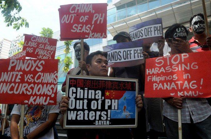 Los manifestantes realizan una protesta al frente del consulado chino en el distrito financiero de Manila el07 de julio, denuncian los reclamos del régimen chino en elMardel Sur de China. Las autoridades chinas podrían pronto comenzar la segunda fase de la construcción de la isla en las aguas en disputa. (Jay Directo / AFP / Getty Images)