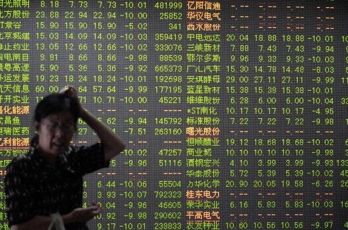 Un inversor en frente de una pantalla que muestra los movimientos del mercado de valores en Hangzhou, provincia oriental china de Zhejiang, el 7 de julio de 2015. (STR / AFP / Getty Images)
