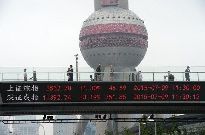 El índice compuesto de Shanghái (arriba) y el Índice Compuesto de Shenzhen se ve al lado de un paso a desnivel frente a la Oriental Pearl Tower en Shanghái el9 de juliode 2015. (STR / AFP / Getty Images)