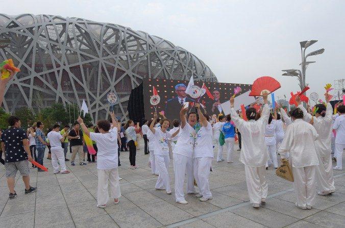 Un grupo de personas celebra ante el Estadio Nido de Pájaro que Beijing haya sido elegida como sede de las Olimpiadas de Invierno 2022. (Xiaolu Chu/Getty Images)