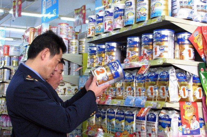 Agentes de policía chinos comprueban las fechas de las latas de leche en polvo en un supermercado en Tongzi, provincia suroccidental china de Guizhou, el 9 de febrerode 2010, debido a que los productos lácteos que contienen la sustancia química industrial melamina han aparecido de nuevo en las tiendas. (AFP / Getty Images)