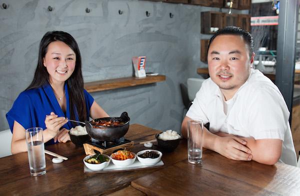 Chef Hooni Kim (R) comparte su jjigae del sundubu — guiso de tofu picante Coreano, con el escritor Li CiCi en su Hanjan de restaurante Flatiron. (Petr Svab/La Gran Época)