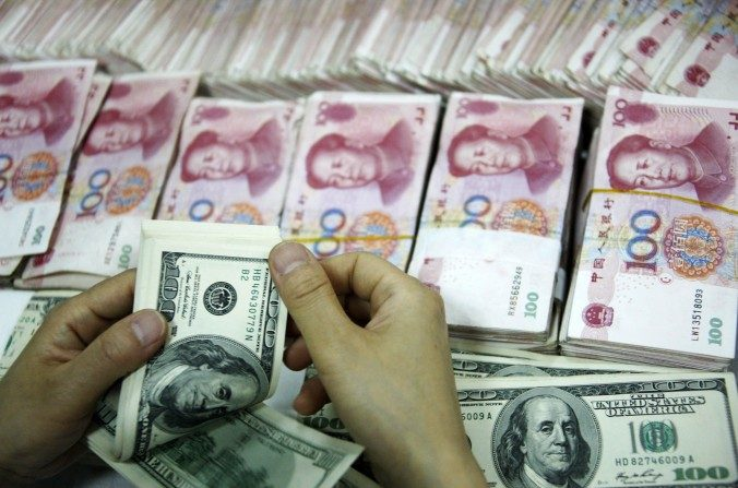 Billetes de dólares estadounidenses se cuentan junto a las pilas de billetes de 100 yuanes chinos (RMB) en un banco en Huaibei, en la provincia oriental china de Anhui, el 23 de septiembre de 2014. (STR / AFP / Getty Images)