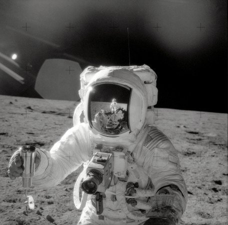 El astronauta Alan L. Bean, piloto del módulo lunar del Apolo 12 en misión de aterrizaje lunar, sostiene un Recipiente Especial Muestra Ambiental llena de suelo lunar recogida durante la actividad extra vehicular (EVA) en la que participaron los astronautas Charles Conrad Jr., comandante, y el participante Bean. Connrad, quien tomó esta foto, se ve reflejado en la visera del casco del piloto del módulo lunar. (NASA)