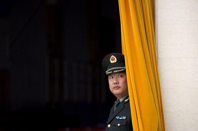 Un miembro del Ejército Popular de Liberación (EPL) espera detrás de una cortina en el Gran Palacio del Pueblo en Beijing el25 de diciembrede 2011. (Ed Jones / AFP / Getty Images)