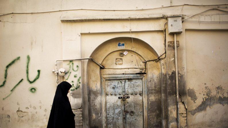 Una mujer pasa junto a una casa abandonada en un antiguo barrio AFP PHOTO / BEHROUZ MEHRI (Photo credit should read BEHROUZ MEHRI / AFP / Getty Images)