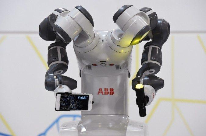 Un robot YuMi sostiene con sus brazos un teléfono inteligente y una linterna en la exhibición de la feria industrial Messe en Hannover, Alemania central, el 13 de abril de 2015. Pocos productos hechos en China llamaron la atención en esta feria. (TOBIAS SCHWARZ/AFP/Getty Images)