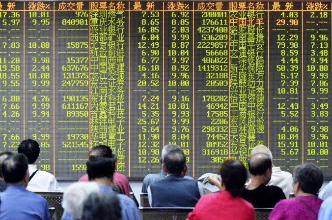 Tanto los índices bursátiles de Shanghái como de Shenzhen cayeron más de un 30 por ciento en tres semanas. En la foto, los inversores se sientan delante de una pantalla que muestra los movimientos del mercado en una empresa de valores en Hangzhou, provincia oriental china de Zhejiang, el8 de juliode 2015. (STR / AFP / Getty Images)