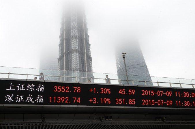 Una pantalla que muestra el índice compuesto de Shanghái (arriba) y el Índice Compuesto de Shenzhen en un paso a desnivel frente al Centro Financiero Mundial de Shanghái (izquierda), Torre Jin Mao (centro) y la Torre Shanghái en Shanghái el9 de juliode 2015. (STR / AFP / Getty Images)
